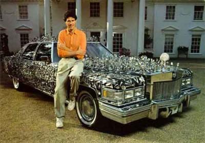 Una curiosa immagine di Uri Geller seduto su un'auto ricoperta dai cucchiai da lui piegati, che si trova al Beaulieu National Museum in Inghilterra.